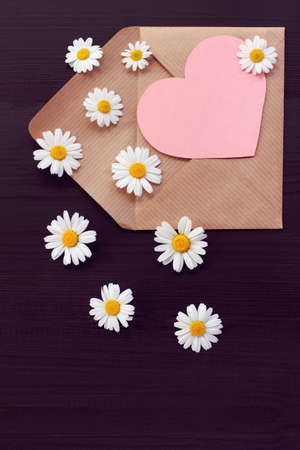open paper envelope with a heart symbol and real daisies. flower love valentine