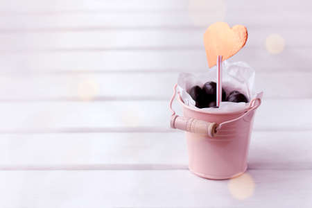 small pink bucket of chocolate dragees and a symbol of the heart. sweet valentine for beloved