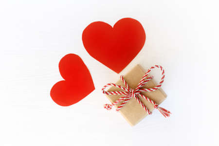 gift box with bow and a pair of red hearts top view. surprise for lovers