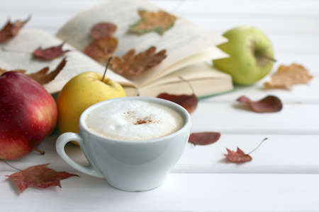 frothy cappuccino on a background of apples, books and fallen leaves on the table front view. warming moments of autumn Reklamní fotografie