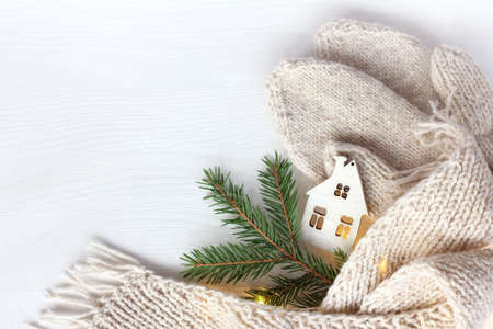 small Christmas-tree decoration in the shape of a house with a light in the window and a fir branch, a scarf and mittens on the table, Top view. warming atmosphere of winter holidays