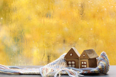 two small houses wrapped in a scarf against the backdrop of an autumn landscape. warming atmosphere of home comfort Reklamní fotografie