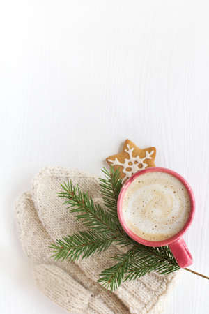 red cup with a foamy cappuccino is decorated with a fir branch and knitted mittens on a table top view. warming Christmas coffee pause Reklamní fotografie