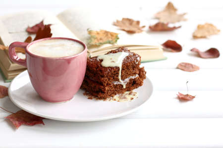 cake with a cup of coffee on a background of books and leaves on the table. sweet warming autumn