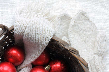 wicker basket with red balls, knitted scarf and mittens on the table top view. warm clothes and decorations for the holiday