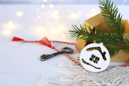 ball-shaped decoration with a house under the Christmas tree next to an open gift and a silver retro key. with a housewarming in the new year