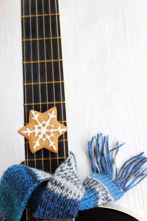 acoustic guitar in a blue scarf with cookies top view. warm melodies for the winter holidays
