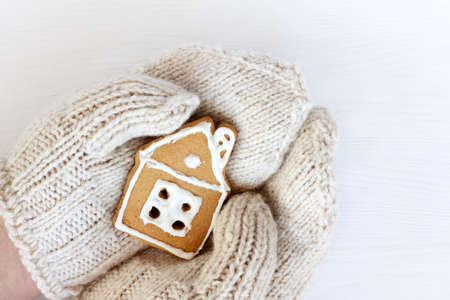 hands in knitted mittens hold a gingerbread house close-up. warm home winter holidays