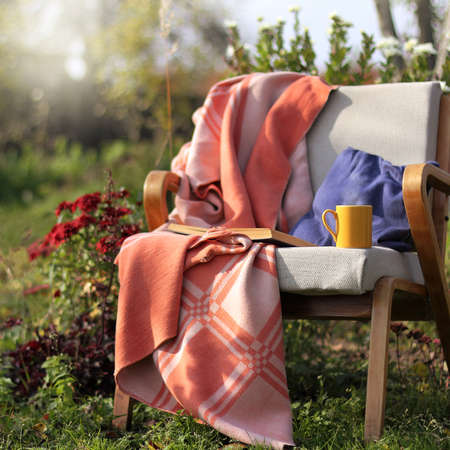 old blanket on an armchair with a book and a cup of hot drink. autumn relaxation in the garden