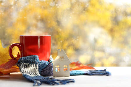 house scarf and mug with a drink on the background of the window after the rain. warming home autumn atmosphere Foto de archivo