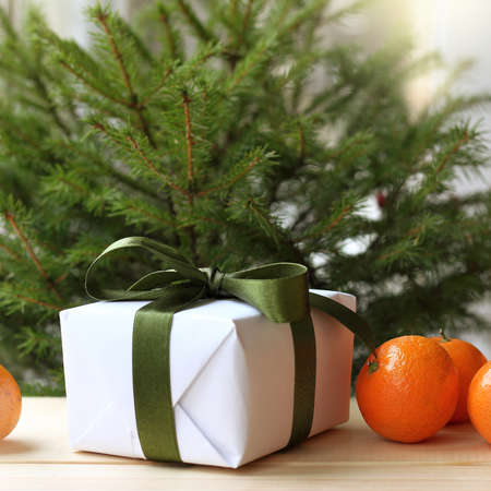 gift with green ribbon and tangerines under the tree. Christmas surprise