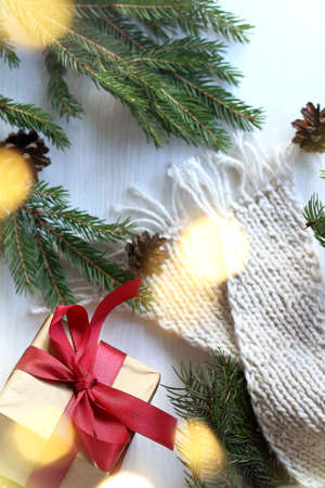 Christmas gift and fir branches with cones and knitted white scarf in blurry garland lights, top view, Flat lay. Xmas greeting card and New Year winter holiday background. Foto de archivo