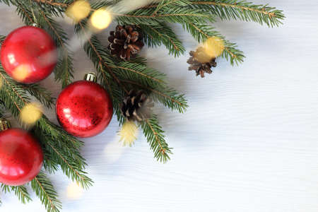 red balls and cones with a glowing garland on a spruce branch. holiday decorations for Christmas