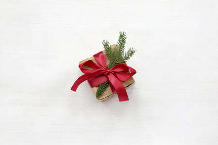 box in craft paper tied with a red ribbon with a bow and decorated with a spruce branch top view on a light surface. holiday gift for Christmas