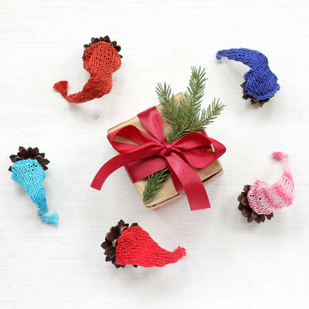 cones in multi-colored caps around a gift decorated with a spruce branch top view. Christmas gnomes dance