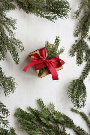 gift decorated with a fir branch and a red bow top view. festive new year surprise Foto de archivo