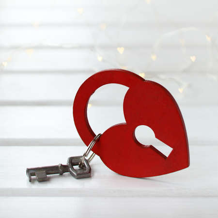 red wooden padlock in the shape of a heart and a metal key. conceptual valentine Foto de archivo
