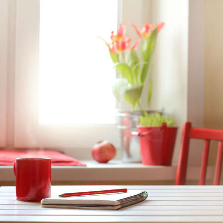 mug on the table with a pencil and a notebook on the background of a window with flowers in the morning. coffee-warming pause in red colors Foto de archivo