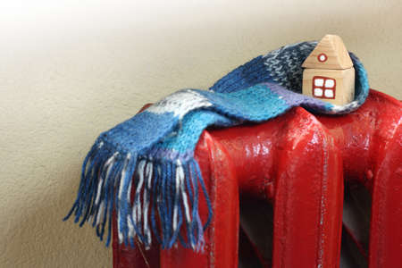 mock up of a wooden house in a blue scarf on a red cast-iron battery. efficient home heating system