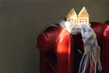 pair wooden house in knitted scarf on a red radiator battery in the sun. complete building heating solutions Foto de archivo