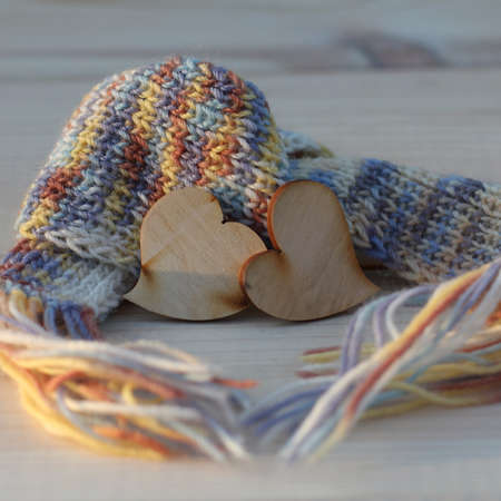 pair of wooden hearts wrapped in a knitted scarf. love warm feelings