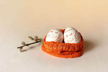 a pair of happy eggs in a nest of orange hats next to a willow tree branch. meet spring together Foto de archivo