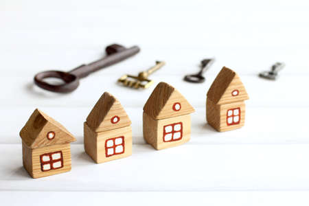 Four wooden houses on the background of blurry silhouettes of different keys. Reservation of individual real estate