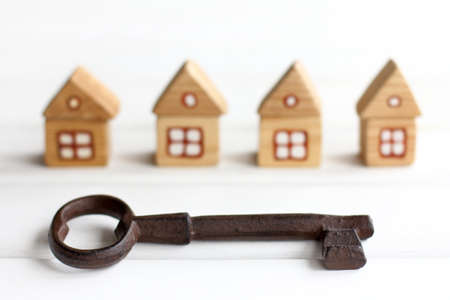 Big iron key on a background of blurry silhouettes of wooden houses. complete solutions for individual real estate