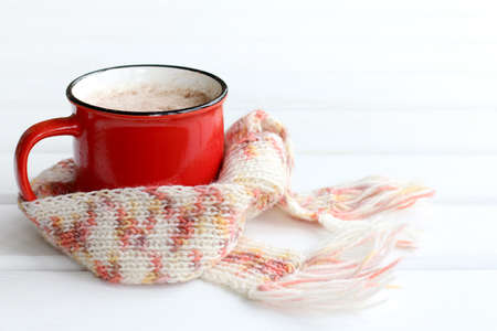 red mug wrapped in a knitted scarf on the table close-up. warming foamy cappuccino
