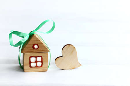 wooden mansion with a green bow and a heart symbol. sweet home as a gift