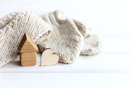 house and a heart made of wood on a background of a scarf and mittens. cute warm house