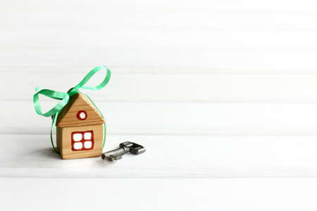 house with a green bow and key on a light background with copy space. new home as a gift