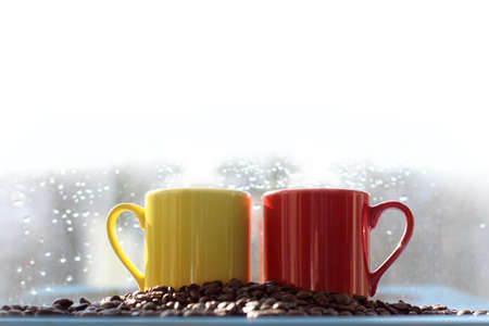 red and yellow mug with coffee beans and white steam on top. hot spot for inscription