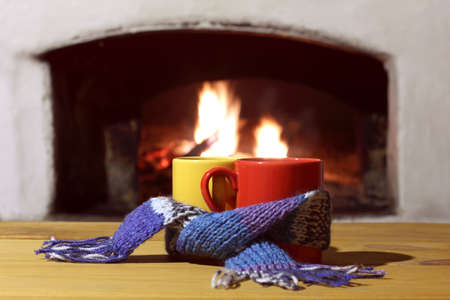 red and yellow mugs wrapped in a blue scarf on the table against the background of a burning fireplace. warming hot drinks