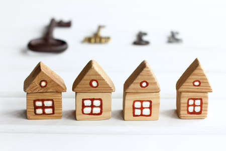 wooden houses with windows and a roof on a background of silhouettes of keys of different sizes. real estate offer