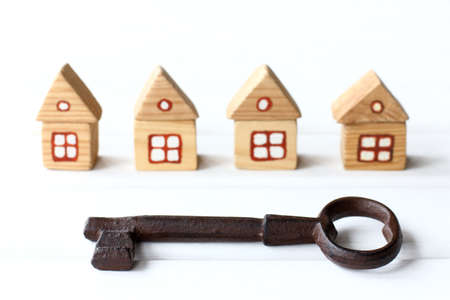 very large iron key on a background of blurry silhouettes of wooden houses. profitable real estate solution 免版税图像