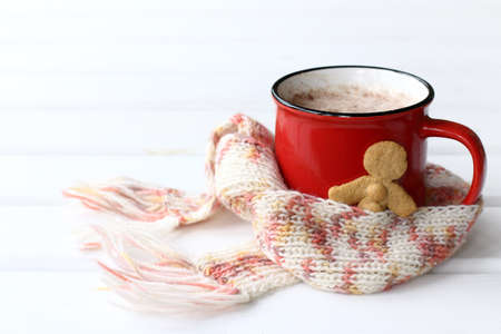 hot drink in a red mug and a ginger man wrapped in a knitted scarf on the table. Warming care in diseases 免版税图像