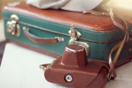 leather retro suitcase and a camera in case lie on the table. going on a nostalgic journey 免版税图像