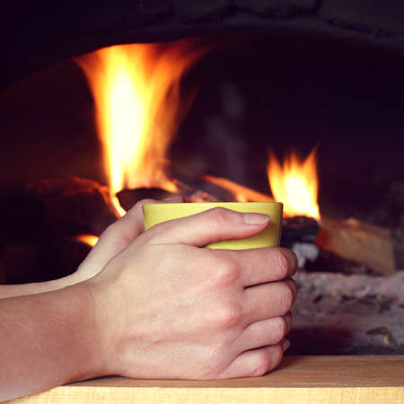 hands are holding a yellow cup on the background of the fireplace. warming atmosphere for recovery