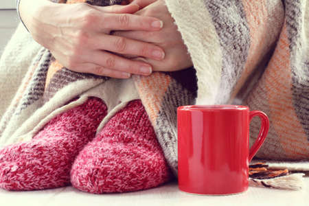 red mug with hot medicine and a man in warm socks is wrapped in a blanket close-up. therapy for colds and viral diseases