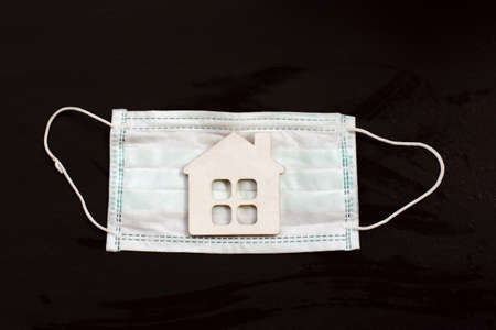 model of the house on a background of a medical mask on a dark background. individual isolation concept 免版税图像