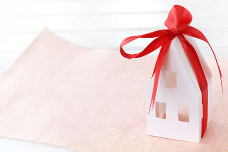 a paper model of the house is wrapped in a red bow and stands on graph paper. start a new life from scratch