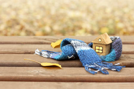 mock up of a wooden house in a warm scarf in the autumn. comfortable living in self-isolation