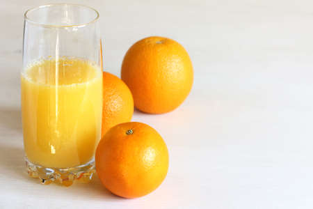 glass with orange juice on a background of oranges on the table front view. freshly squeezed natural drink
