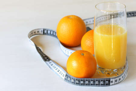 glass with orange juice and orange fruits with a measuring tape on the table. healthy diet for weight loss