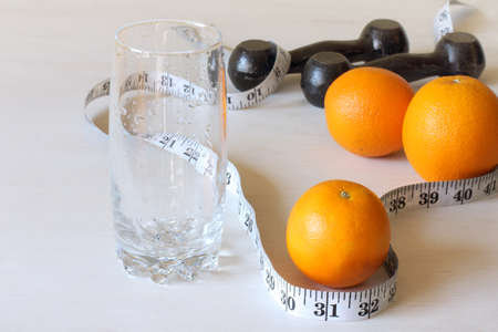 oranges, an empty glass with a measuring meter and dumbbells on the table. fruit diet and sports
