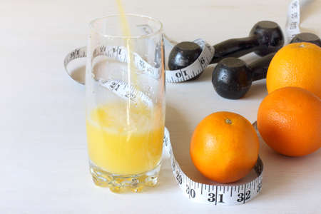 pouring orange juice into a glass next to the fruit meter and dumbbells. body reinforcement with natural vitamins