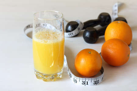 orange juice in a glass on a background of dumbbells and a centimeter. fitness and natural nutrition