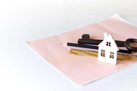 mock-up of a white house on graph paper on a background of a pencil, key and ruler. Plot Design, Construction Zdjęcie Seryjne