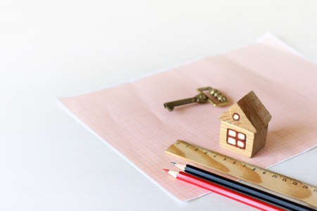 mock up of a wooden house on graph paper with pencils, a golden key and a ruler. house with turnkey plot Zdjęcie Seryjne